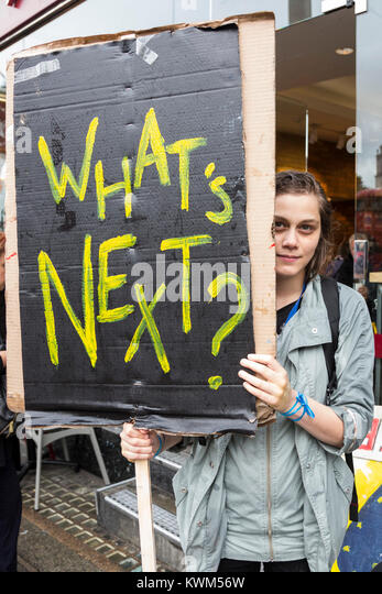 Young woman holding up a What's Next poster at an Anti-Brexit protest in Central London - Stock Image