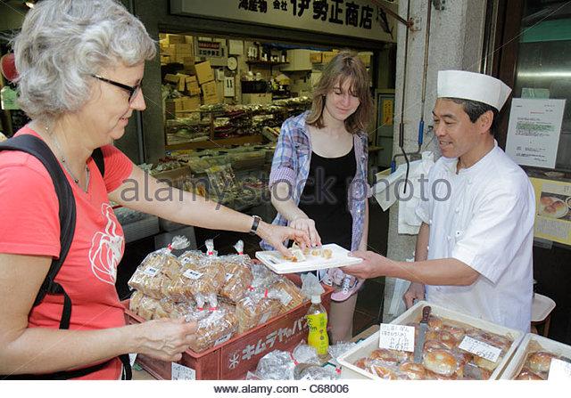 Tokyo Japan Tsukiji Fish Market shopping kanji hiragana characters for sale display fresh food vendor pastries buns - Stock Image