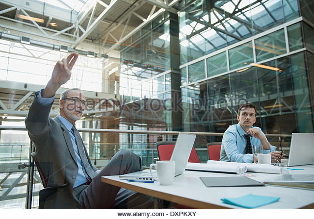 Businessman with arm raised in conference room meeting - Stock Image