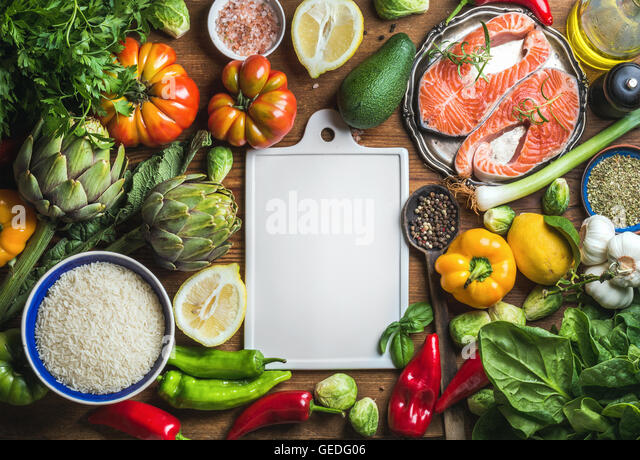 Raw uncooked salmon fish in small metal plate with vegetables, rice, herbs, spices, olive oil on rustic wooden background, - Stock Image