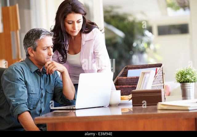 Worried Hispanic Couple Using Laptop On Desk At Home - Stock-Bilder