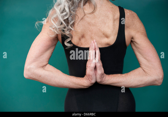 Senior woman back with her hands in yoga mudra namaste. - Stock Image