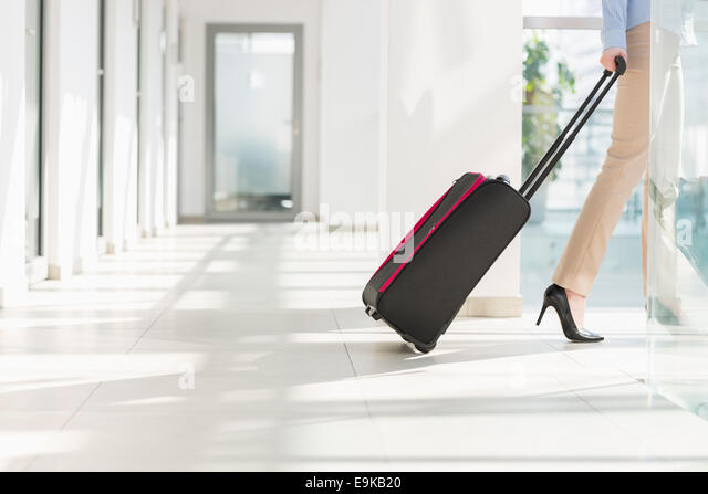 Low section of businesswoman with luggage leaving airport - Stock-Bilder