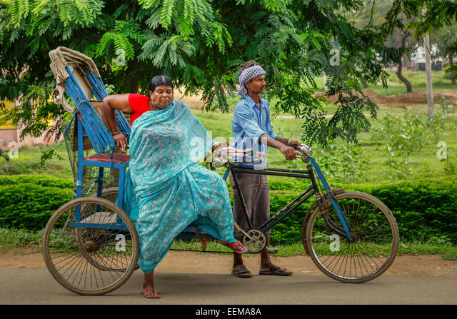 Sari-clad woman gets off cycle rickshaw on Bodhgaya street, Bihar, India. - Stock Image