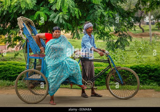 Sari-clad woman gets off cycle rickshaw on Bodhgaya street, Bihar, India. - Stock Image