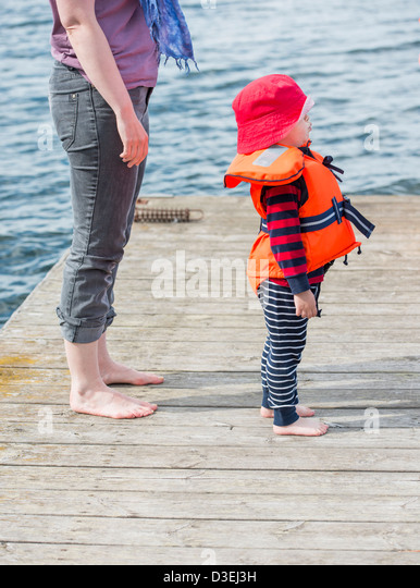 Adult caucasian woman standing barefoot next to her young child on a wooden jetty by the sea - Stock Image