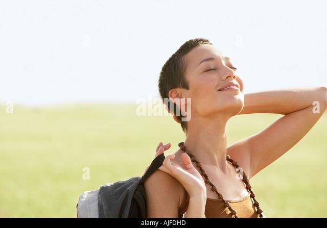 Female hiker basking in sun, standing in field - Stock Image