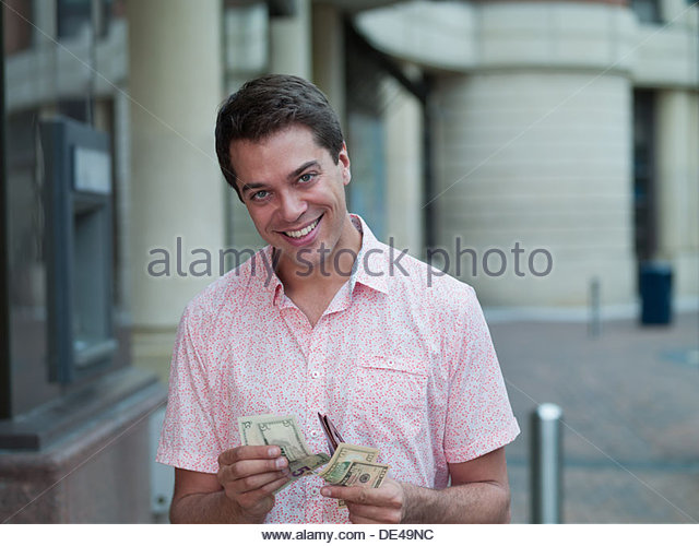 Smiling man counting money near ATM machine - Stock Image