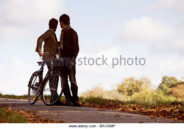 A young couple standing with a bicycle in autumn time - Stock Image