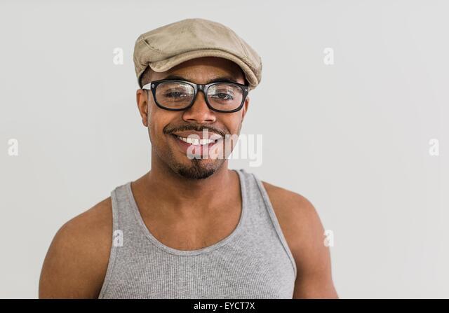 Studio portrait of mid adult man wearing flat cap - Stock Image