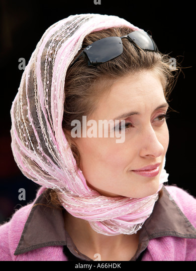 Portrait of girl woman wearing pink scarf and Ray Ban sunglasses with dark background trendy pink plus  brown color - Stock Image