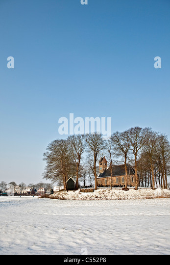 The Netherlands, Hijum, Church on mound in snow. - Stock Image