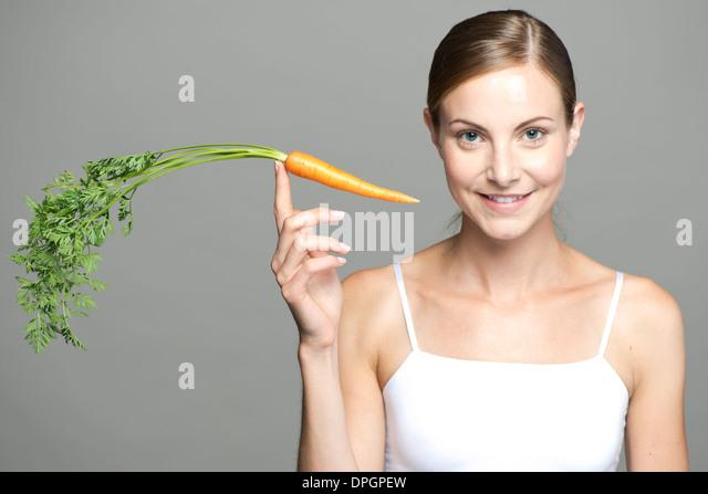 Young woman balancing carrot on fingertip - Stock Image