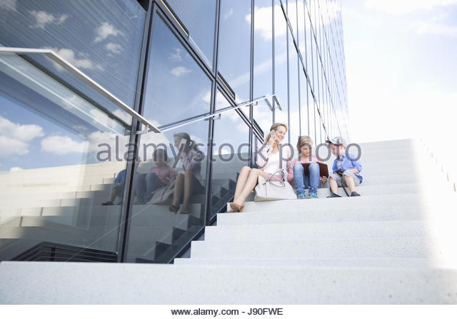 Businesswoman Mother On Phone With Children Outside Office - Stock-Bilder