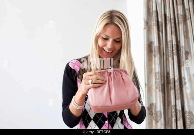 Attractive blond woman looking in purse - Stock Image