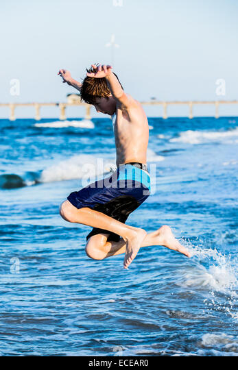 Redhead boy on the beach jumping in the surf - Stock Image