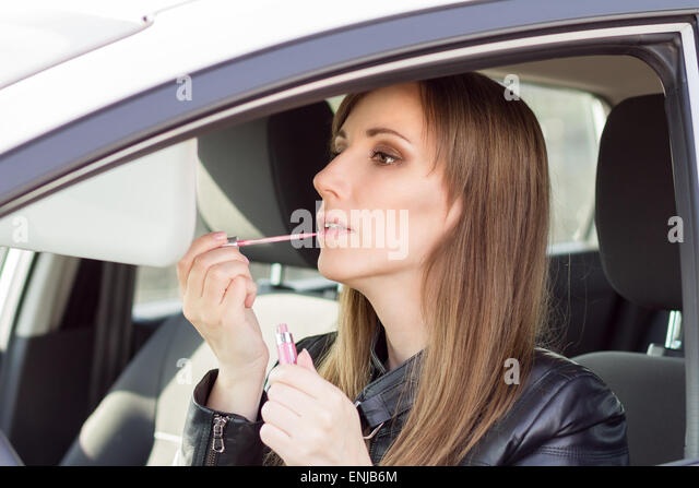 Young pretty woman apply makeup in car. Businesswoman with lipstick in automobile - Stock Image