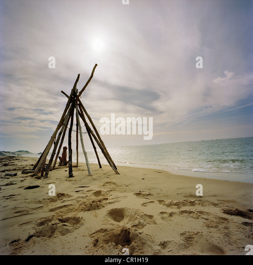 Log teepee on sandy beach - Stock Image