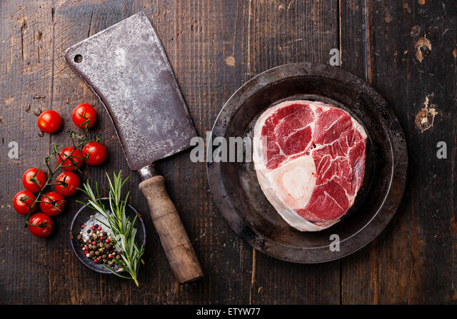 Raw fresh cross cut veal shank for making Osso Buco and meat cleaver on dark wooden background - Stock Image