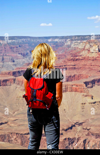 Woman alone stands gazing into the distance at the North Rim of the Grand Canyon, Arizona - Stock Image