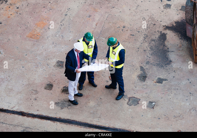 Workers reading blueprints at dry dock - Stock Image