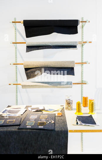 Denim fabric rolled on racks with worktable in foreground - Stock Image
