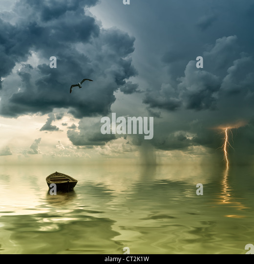 The lonely old boat at the ocean, comes nearer a thunder-storm with rain and lightning on background - Stock Image