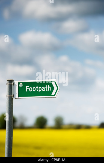 Footpath sign in front of a rape field in the English countryside - Stock-Bilder