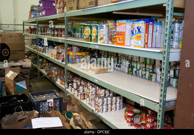Donated can goods and cereal on shelves at food bank - Virginia USA - Stock Image