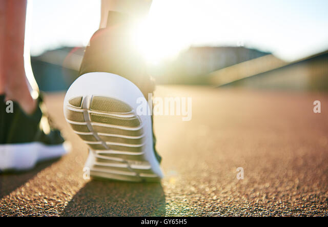 Close up low angle view of running shoes with while soles on an empty road as the sun highlights the distance - Stock Image