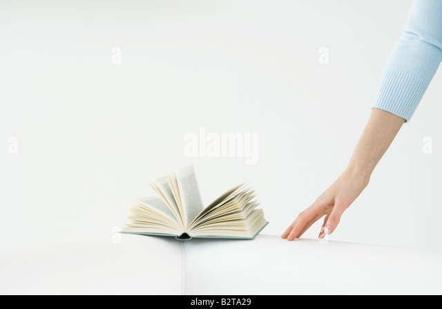 Arm reaching for book, flipped open - Stock-Bilder