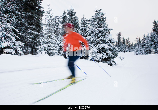 A young woman cross-country skiing. (blurred motion) - Stock Image
