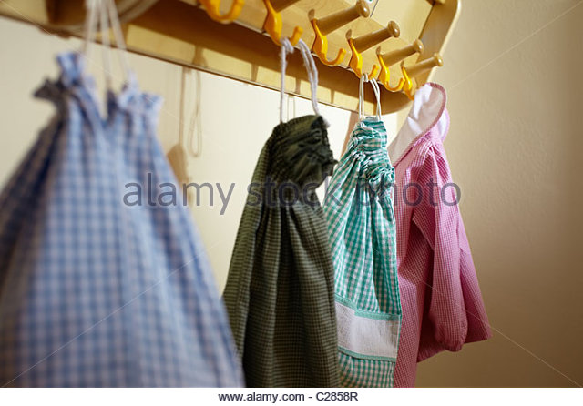 Group of colorful bags on hanger at preschool. Horizontal shape, focus on background - Stock Image