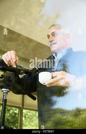 Senior man at home, drinking coffee, using telescope through window - Stock-Bilder