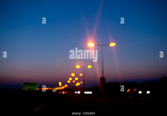 A motorway with street lights at dusk - Stock Image