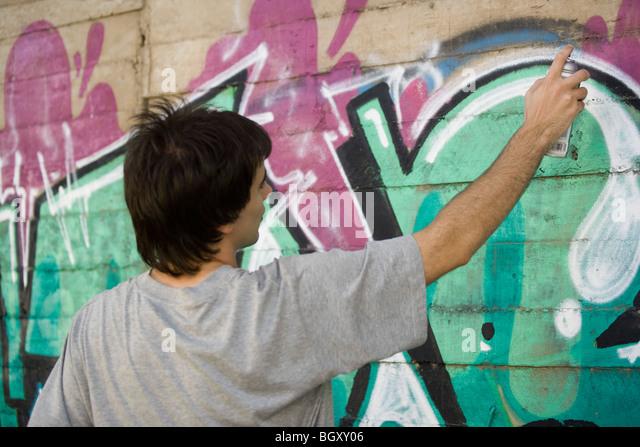 Young man spray painting graffiti mural - Stock Image