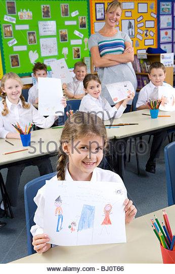 Proud school children showing off drawings in classroom - Stock-Bilder