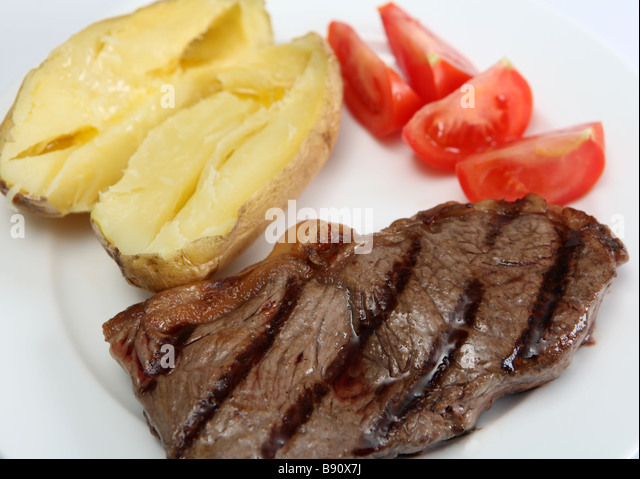 A grilled New York striploin or porterhouse steak names vary from place to place served with baked potato and fresh - Stock-Bilder