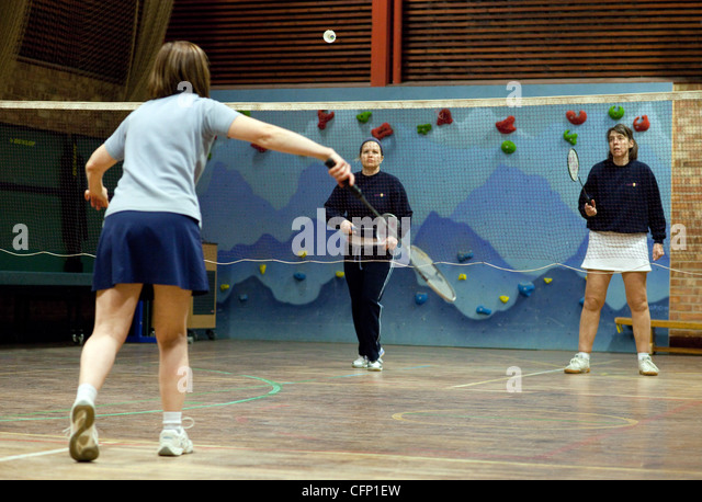 Three women playing a game of badminton, Newmarket Suffolk UK - Stock Image