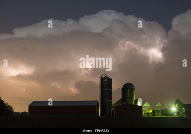 Town Of Wallkill, N.Y, USA. 19th May, 2015. Lightning flashes in the clouds above the barn and silos of a farm in - Stock Image