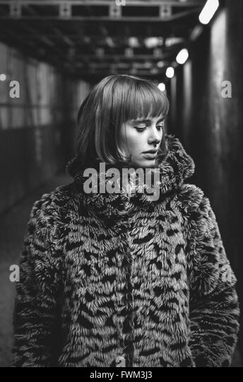 Beautiful Young Woman Wearing Fur Coat Standing In Subway - Stock Image