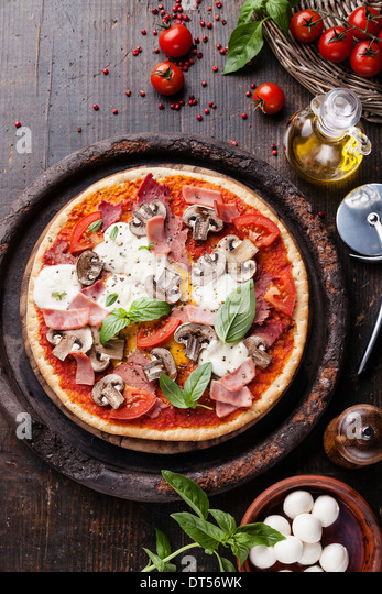 Italian pizza with meat, ham and mushrooms on wooden table - Stock Image