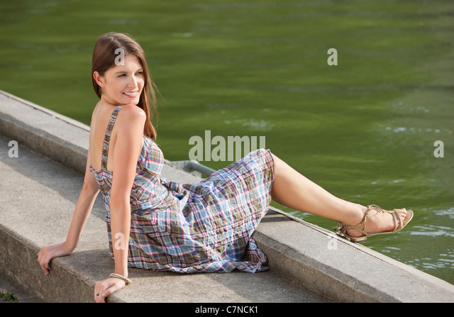 Woman sitting at the ledge of a canal and smiling, Paris, Ile-de-France, France - Stock Image