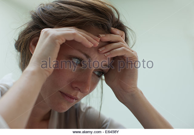 Depressed woman with head in hands - Stock Image