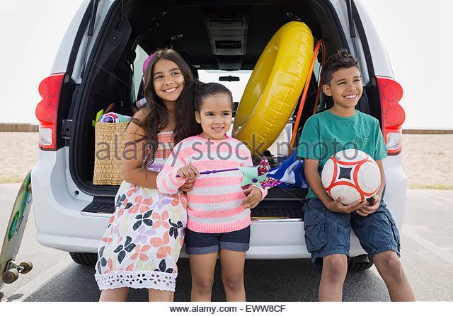 Smiling brother and sisters van arriving at beach - Stock Image