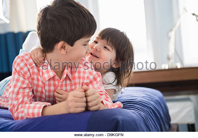 Girl hugging her brother - Stock Image