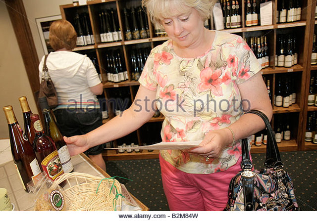 Michigan Traverse City Old Mission Peninsula Chateau Grand Traverse winery vineyard bottles purchase woman women - Stock Image