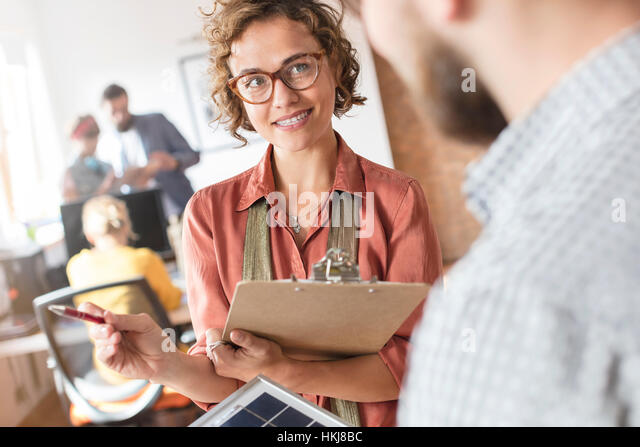 Design professionals with clipboard talking in office - Stock-Bilder