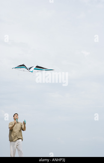 Man flying kite, looking up, three quarter length - Stock Image