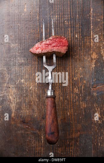 Piece of beef steak on meat fork on wooden background - Stock Image